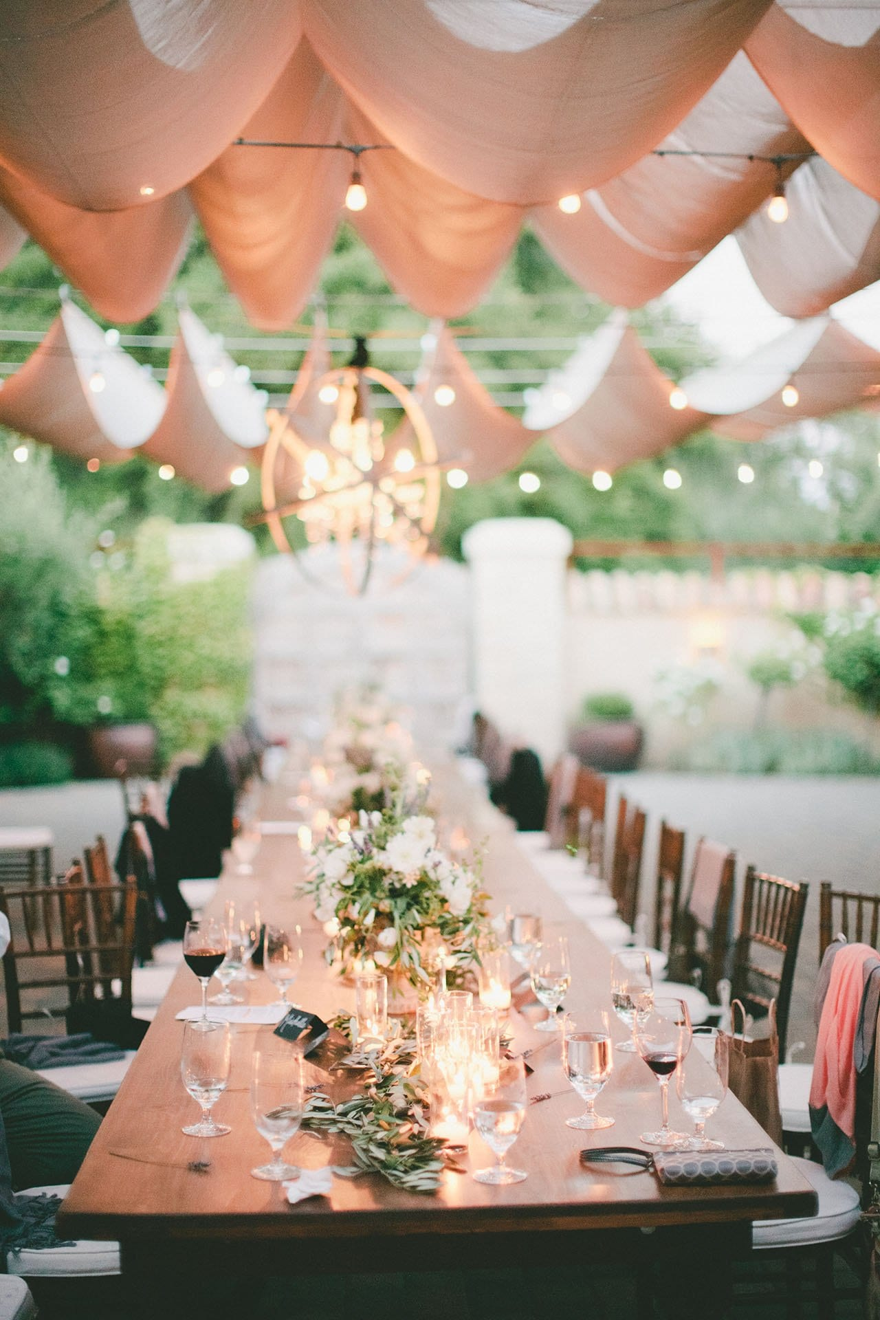 Seven Branches Venue and Inn - Dining Courtyard with long wooden table and chairs with lights flowers and wine glasses